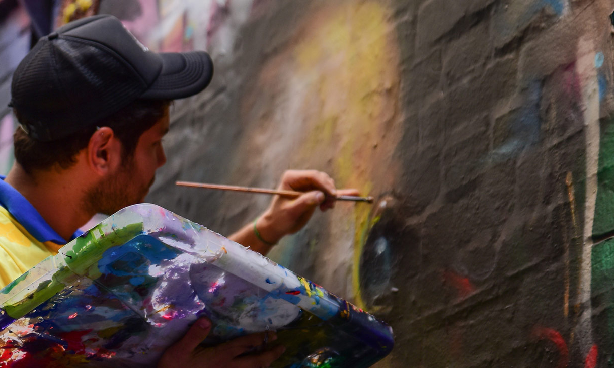 Main uses artist paintbrush on brick wall