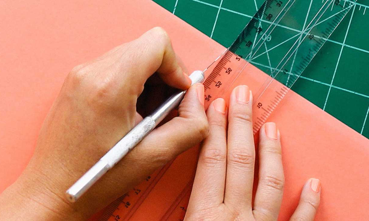 Hands cutting paper card with ruler