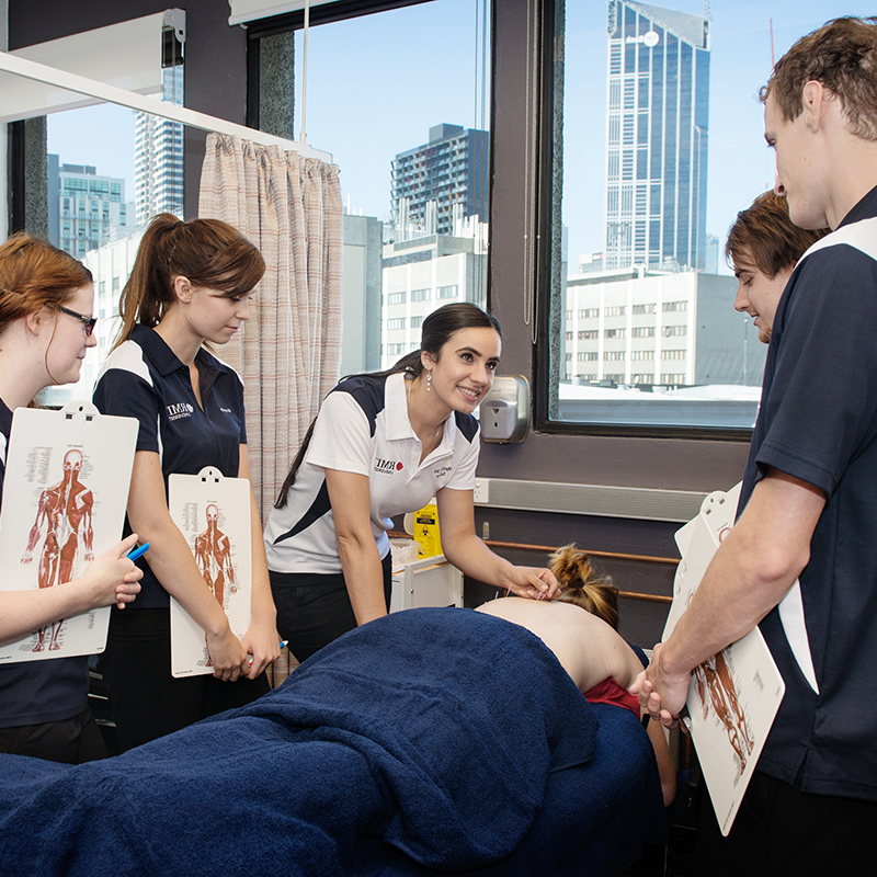 A group of students and teacher around a person receiving acupuncture